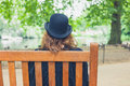 Woman wearing bowler hat in park on bench Royalty Free Stock Photo