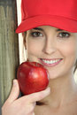 Woman wearing a cap and eating an apple Stock Photos