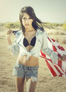 Woman wearing denim shirt holding american flag beautiful young in the open desert image contains scratches and noise as part of Stock Photos