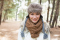 Woman wearing fur hat with woolen scarf and jacket in woods portrait of a beautiful the Stock Photos
