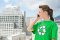 Woman wearing green recycling tshirt talking on the phone outside a sunny day Stock Images