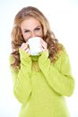 Woman wearing green sweater drinking from mug cozy blond Royalty Free Stock Photo