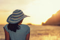 Woman wearing hat admire the sunset over the sea Royalty Free Stock Photo
