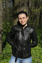 Woman wearing leather jacket and glasses leaning on tree a young caucasian in a black in the forest during early spring Stock Photography