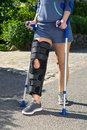 Woman wearing a leg brace walking on crutches with adjustable side panels to immobilize and support her knee after surgery Stock Photo