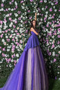 woman wearing long purple dress posing in the flowered garden Royalty Free Stock Photo