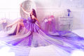 Woman wearing long purple dress posing in studio interior Royalty Free Stock Photo