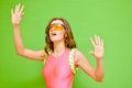 Woman wearing lycra jumpsuit and protect glasses young pink big on green background closeup og girl rising hands with open mouth Stock Photography