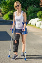 Woman wearing an orthopaedic leg brace with adjustable straps to immobilise her following surgery or accident walking on Royalty Free Stock Photos