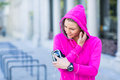 A woman wearing a pink jacket using her phone
