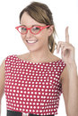Woman wearing red framed glasses holding up finger young Royalty Free Stock Photo