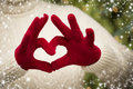 Woman wearing red mittens holding out a heart hand sign in sweater with seasonal with her hands with snow flakes border Royalty Free Stock Photo