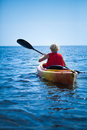 Woman wearing a safety vest heading out to sea alone young on calm water Royalty Free Stock Image