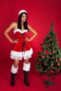 Woman wearing santa claus costume standing near christmas tree beautiful Royalty Free Stock Images