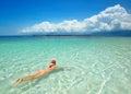 Woman is wearing Santa hat in bikini and swim in water at beach. Royalty Free Stock Photo