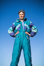 Woman wearing ski suit with hands on hips with blue sky behind Stock Photography