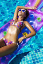 Woman wearing sunglasses and bikini poses swimming on mattress in pool. Phuket island, Thailand Royalty Free Stock Photo