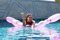 Woman wearing sunglasses and bikini poses swimming on mattress in pool. Phuket island, Thailand Royalty Free Stock Photo