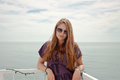 Woman wearing sunglasses in front of ocean smiling and clouds Royalty Free Stock Photography