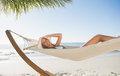 Woman wearing sunhat and bikini relaxing on hammock smiling at camera the beach Royalty Free Stock Photography