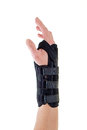 Woman wearing supportive brace on wrist close up of person black secured with velcro straps in studio with white background Stock Image
