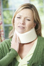 Woman wearing surgical collar in pain at home Royalty Free Stock Images