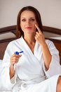 Woman wearing a white bathrobe beautiful young and applying body lotion Stock Photos