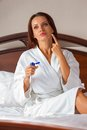 Woman wearing a white bathrobe beautiful young and applying body lotion Royalty Free Stock Images