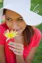 Woman wearing a white hat while smelling a flower Royalty Free Stock Image