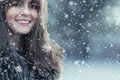 Woman wearing winter clothes cold weather portrait of a smile young in a snow day girl fur and looking in camera trough snowflakes Stock Photos