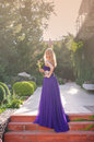 Woman wears long purple dress.