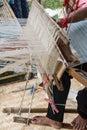 Woman weaving silk in traditional way at manual loom. Royalty Free Stock Photo