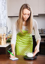 Woman weighing cottage cheese on kitchen scales in apron Stock Images