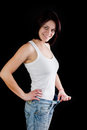 Woman weight loss attractive caucasian with big jeans on black background Stock Image