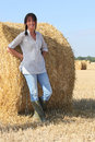 Woman in wellington boots standing a field of hay Royalty Free Stock Image