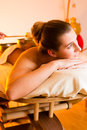 Woman at wellness massage with singing bowls in and spa setting having a bowl therapy Stock Photo