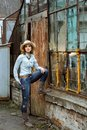 Woman in western wear in cowboy hat, jeans and cowboy boots. Royalty Free Stock Photo