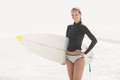 Woman in wetsuit holding a surfboard on the beach Royalty Free Stock Photo