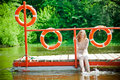 Woman wetting her feet in the river young sitting on a platform Stock Photography