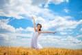 Woman in wheat field with arms outstretched Stock Photo