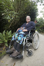 Woman in wheel chair smiling at the camera a inside of a large garden on a rocky pathway Stock Image