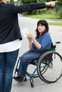 Woman on wheelchair asking a passerby about directions young women female Stock Images