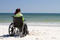 Woman wheelchair beach disabled sits alone in a on a sandy watching the ocean waves Stock Images