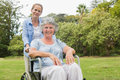 Woman in wheelchair with her daughter smiling at camera the park Royalty Free Stock Images