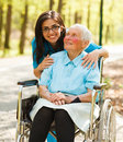 Woman in wheelchair and a nurse kind taking care of elderly lady patient Stock Photos
