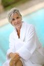 Woman in white bathrobe enjoying pool portrait of smiling senior sitting by resort Stock Photo