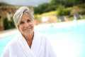 Woman with white bathrobe enjoying spa resort portrait of smiling senior sitting by pool Stock Images