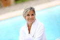 Woman with white bethrobe sitting near pool portrait of smiling senior by resort Royalty Free Stock Photography