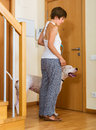 Woman with white big dog young female owner dogo argentino on leash staying at door Royalty Free Stock Photos