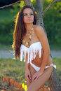 Woman in white bikini posing outdoors a young brunette Royalty Free Stock Photography